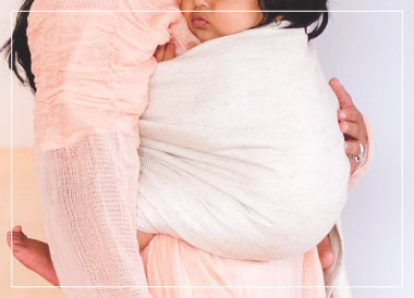 A mom wearing her baby using a woven wrap